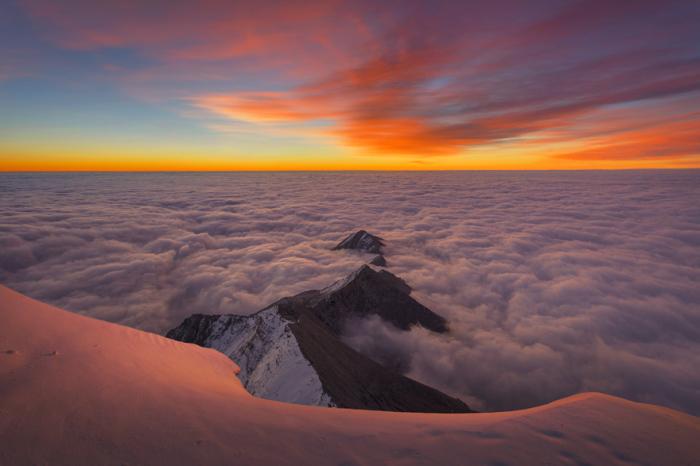 Восхитительный восход солнца освещает удивительное море из облаков, среди которых плывут острые пики горных вершин.