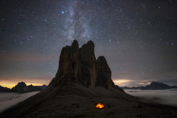 Звездная полоса Млечного пути как будто встречается с величественными скалами Альп, пересекаясь с редкими облаками в вечернем небе.