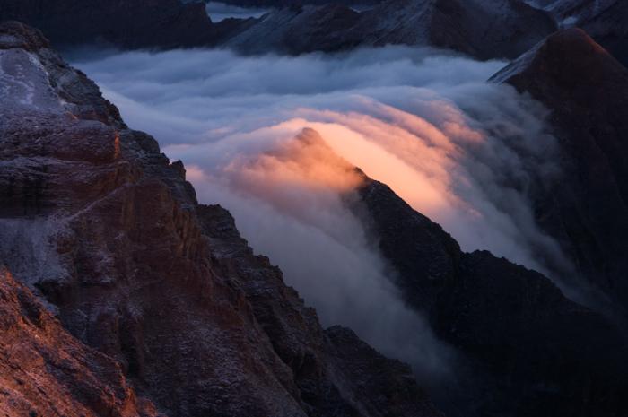 Свет восходящего света среди облачной реки, которая извивается над крутыми горными хребтами, кажется настоящим проявлением магии природы.