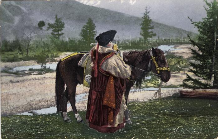 Женщина алтайка стоит возле лошади в куараан борук (головной убор), тон (шуба из овчины)  и  чегедек (безрукавке).