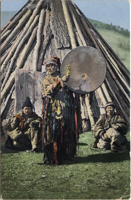 Алтайский шаман играет на бубне возле традиционного жилища - чаадыр.
