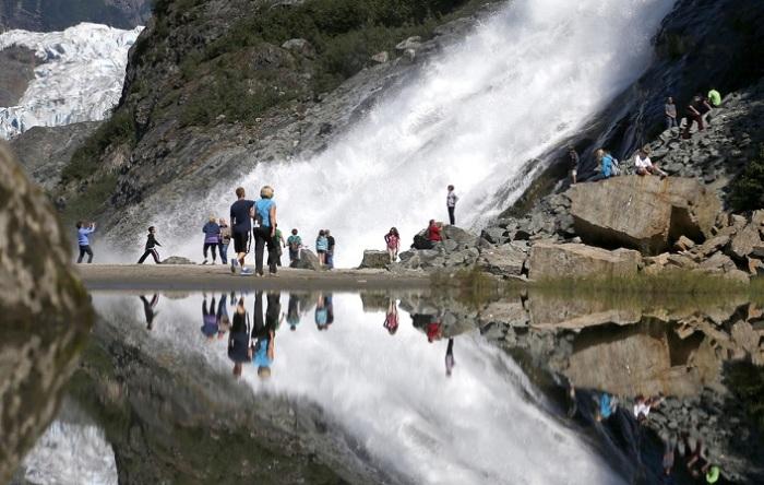 Туристы и их отражение на леднике Менденхолл.