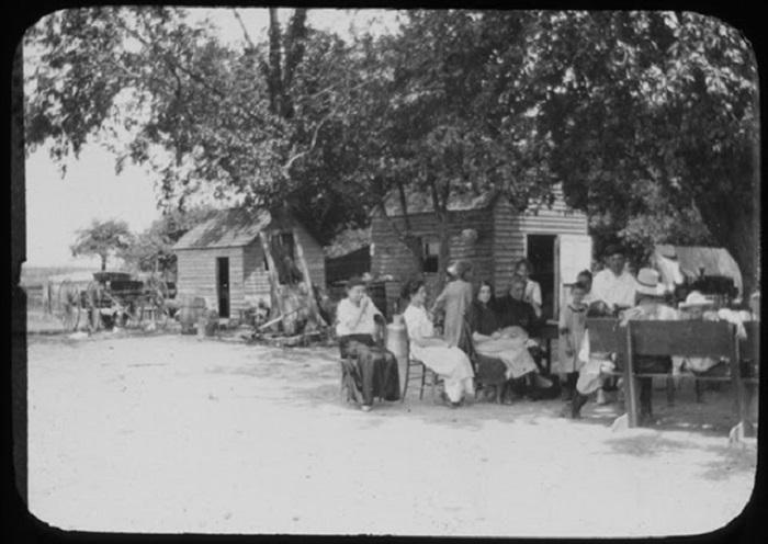 Женщина со своими детьми у дома.