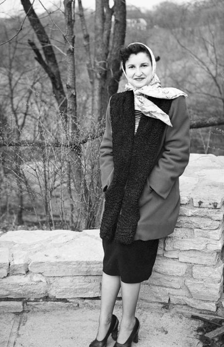 Женщина в пальто с каракулевыми вставками, заменяющих воротник.