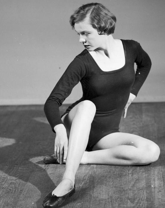 Девушка в черном гимнастическом купальнике готова показать элементы акробатики.