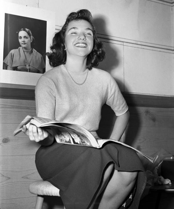 Девушка с вьющимися волосами и веселым настроением читает журнал.