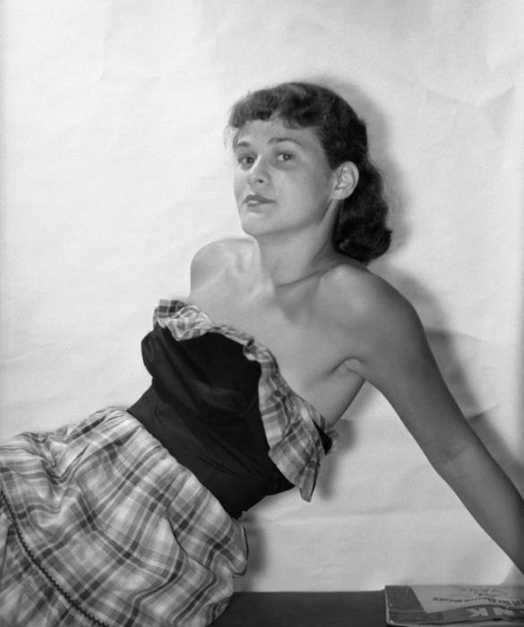 Привлекательная женщина в клетчатой юбке и волнистыми оборками по линии груди.