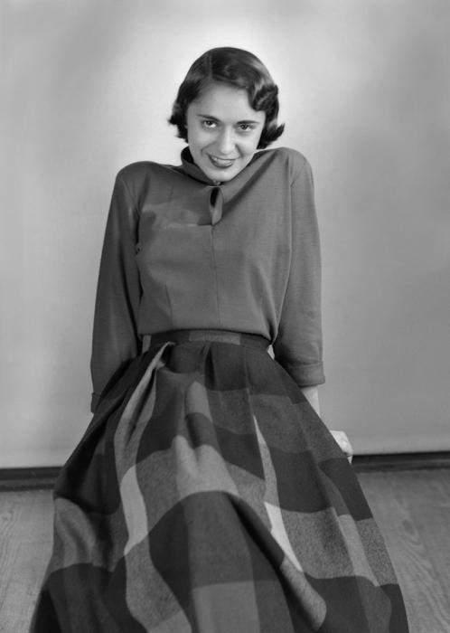 Девушка в блузке и клетчатой юбке темных тонов, которые удобны в использовании.