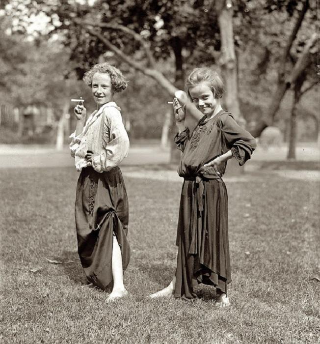 Девочки в платьях позируют с сигаретой.