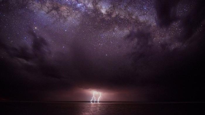 Феноменальное природное световое шоу — молнии, бьющие из мрачных туч — соседствует со звездами Млечного Пути над ними.