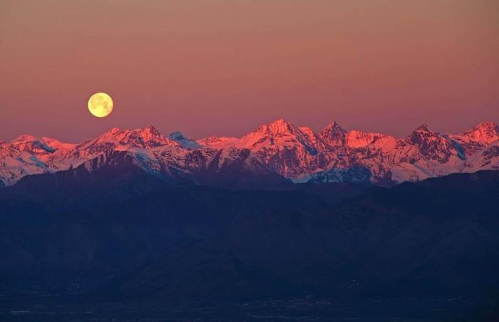 Величественный вид полной луны, взошедшей над розовыми пиками гор.