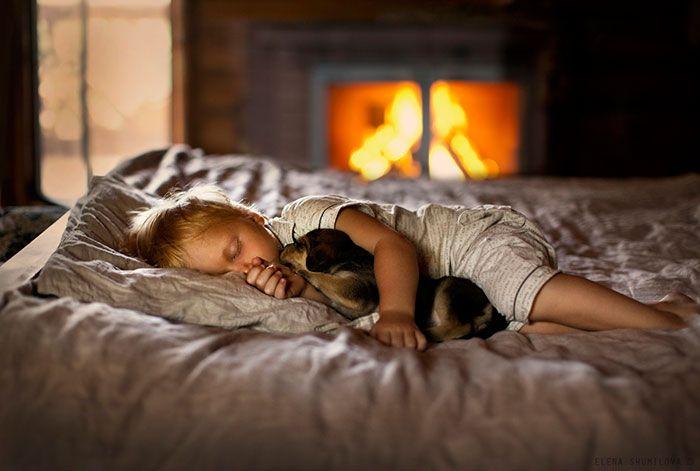 Ребенок спит в обнимку с щеночком.