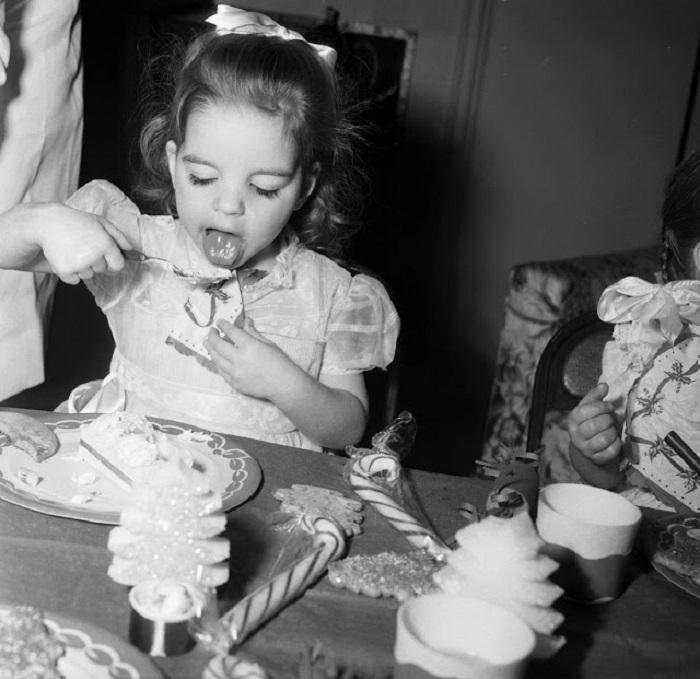 Лайза ест мороженое на рождественской вечеринке в доме Эдгара Бергена, куда она пошла с матерью Джуди Гарленд.