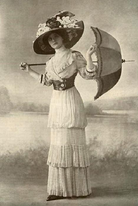 Девушка в шляпе, украшенной огромными цветами.