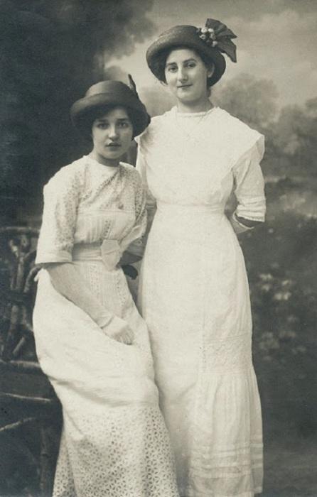 Девушки в платьях с завышенной талией, узкими рукавами, прямой юбкой, немного расширяющейся книзу за счёт небольшого трена.