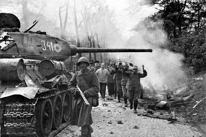 Советский танк Т-34-85 из 7-го гвардейского танкового корпуса и пленные ополченцы из фольксштурма на улицах Берлина.