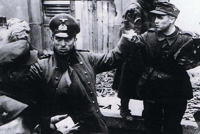 Советский офицер проверяет документы сдавшихся в плен немецких военнослужащих. Берлин, апрель-май 1945 г.