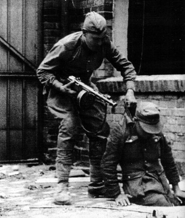Советский солдат вытаскивает из люка немецкого солдата.