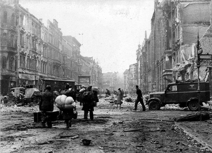 Немецкие мирные жители идут по разрушенной Фридрихтрассе в Берлине.