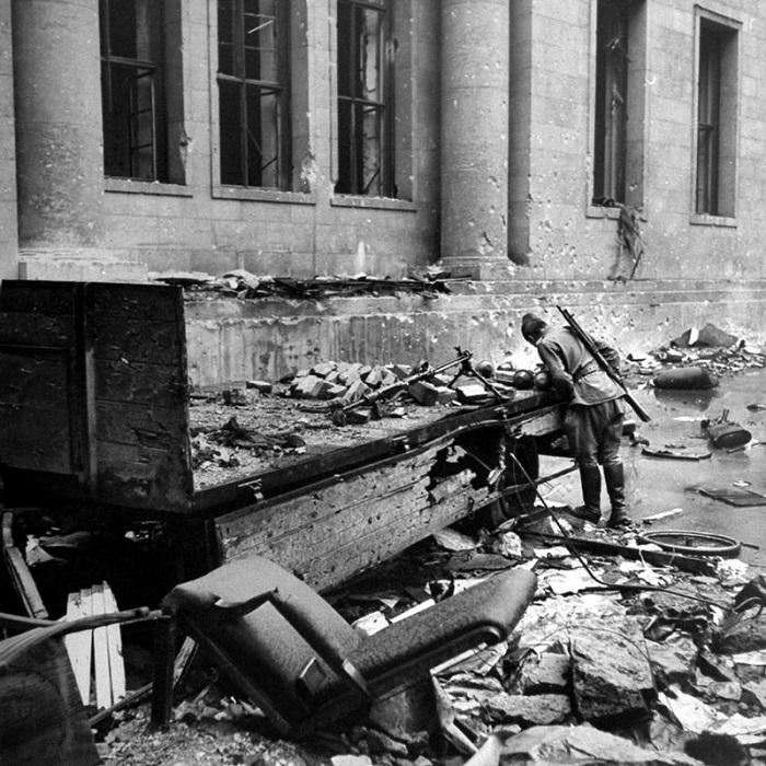 Советский солдат рассматривает фаустпатроны на прицепе возле здания Рейхсканцелярии в последние дни боев в Берлине.