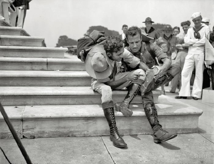 Бойскауты рассматривают свои ботинки после 8000 миль похода во время участия в первом Boy Scout Jamboree. 1937 год.