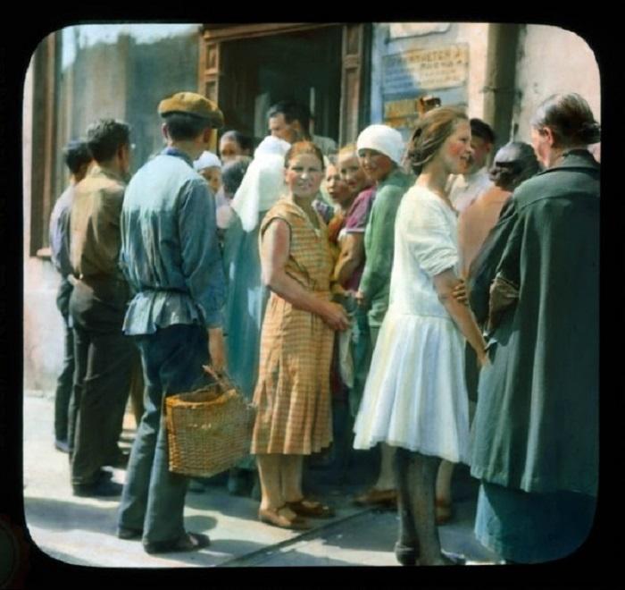 Москвичи стоят в очереди в магазин со спокойными и добрыми лицами.
