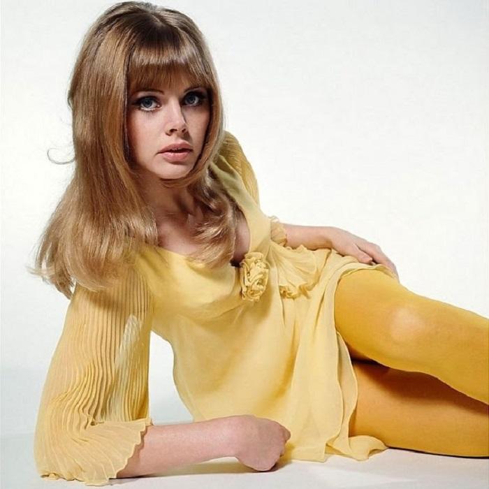 Шведская актриса и фотомодель в легком желтом платье и колготках позирует для страниц модного журнала.