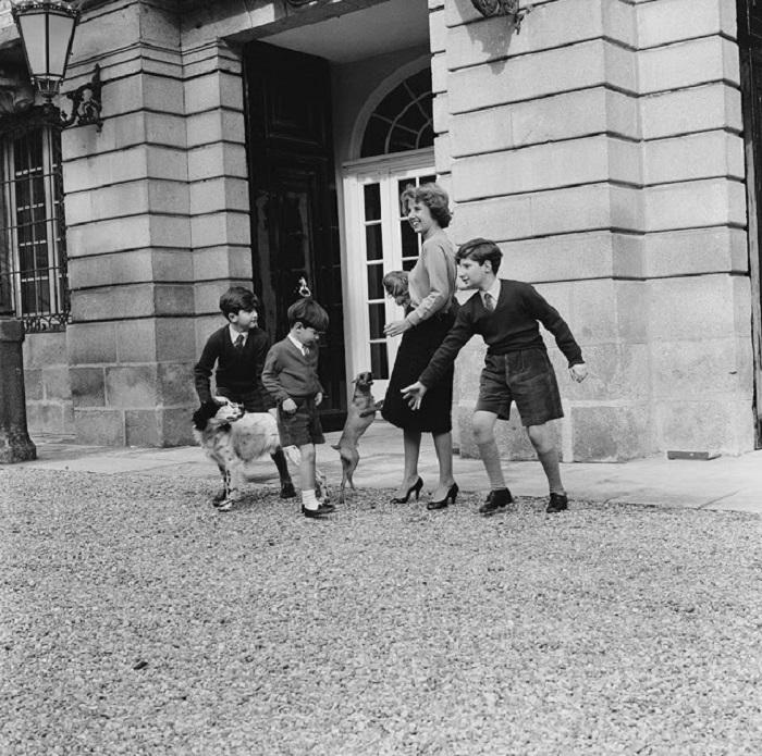 Герцогиня со своими детьми и питомцами во дворе своего дома.