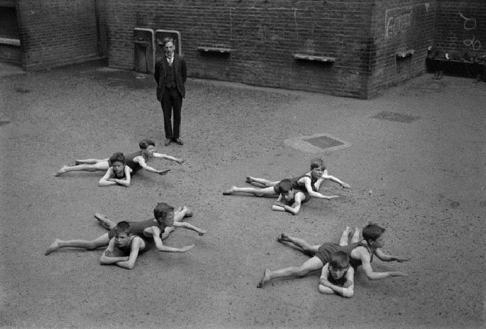 Дети, не имеющие доступа к воде, учатся плавать на школьном дворе. 1920-е годы.