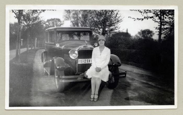 Леди в белоснежном платье позирует сидя на автомобиле.
