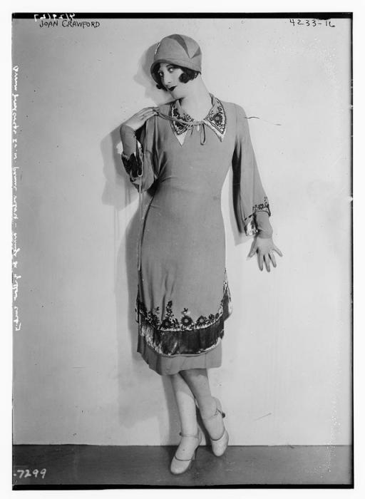 Женщина с короткой стрижкой в оригинальном платье с вышивкой.