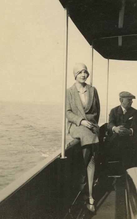 Женщина в костюме и фетровой шляпе на палубе.