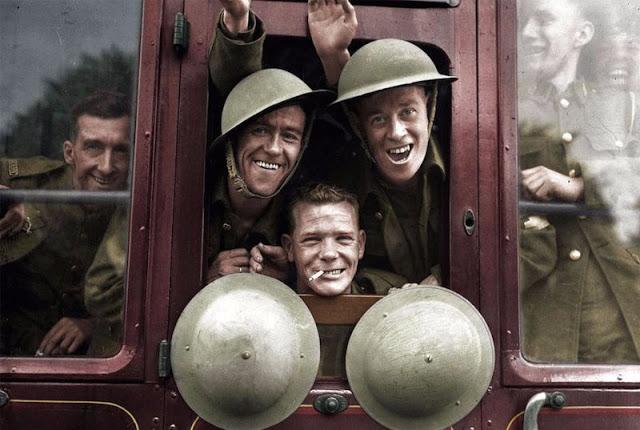 Военные улыбаются из окна поезда во время отправки на Западный фронт.