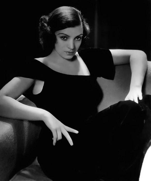 Знаменитость позирует сидя в тёмном платье с необычным вырезом.