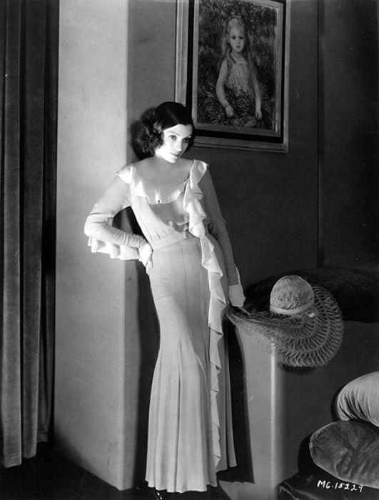 Белый наряд с рюшами и шляпа лежащая рядом, создаёт необычный и лёгкий образ.