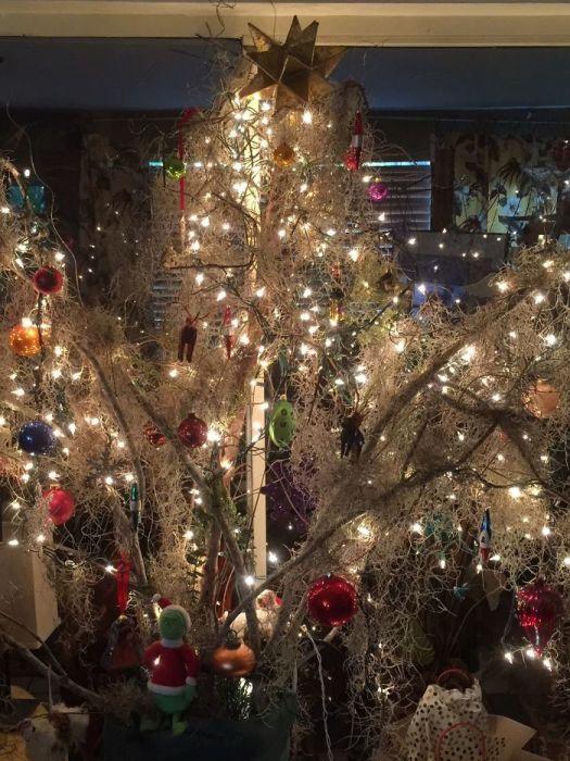 Яркая вторая жизнь пострадавшего от урагана дерева – немного испанского моха, новогодних украшений и огоньков.