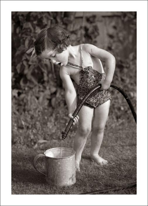Маленькая девочка точит воду для полива рассады.