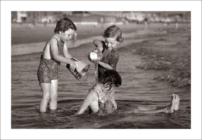 Малыши поливают из детских ведерок.