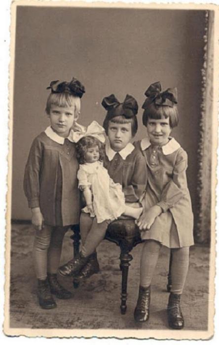 Элегантные сестры с огромными бантами и куклой, Латвия, 1937 год.