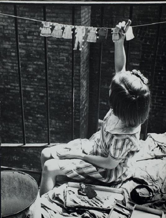 Девочка сушит детскую одежду на веревке, 1935 год.