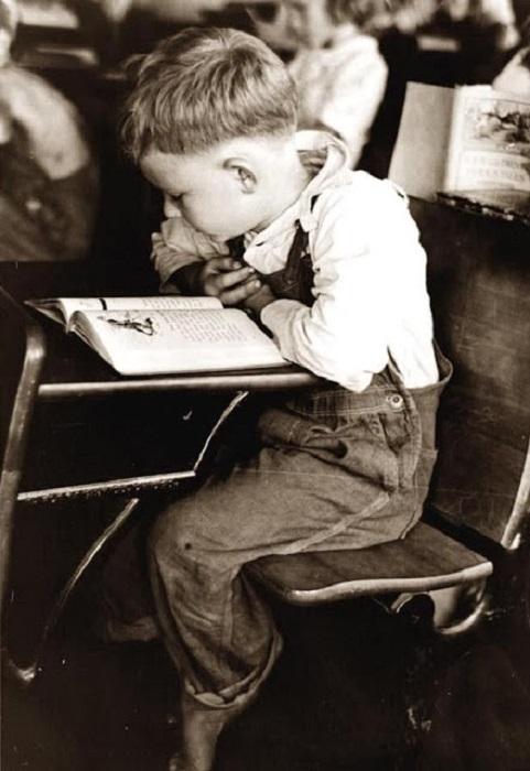 Мальчишка читает в школе за партой, 1938 год.