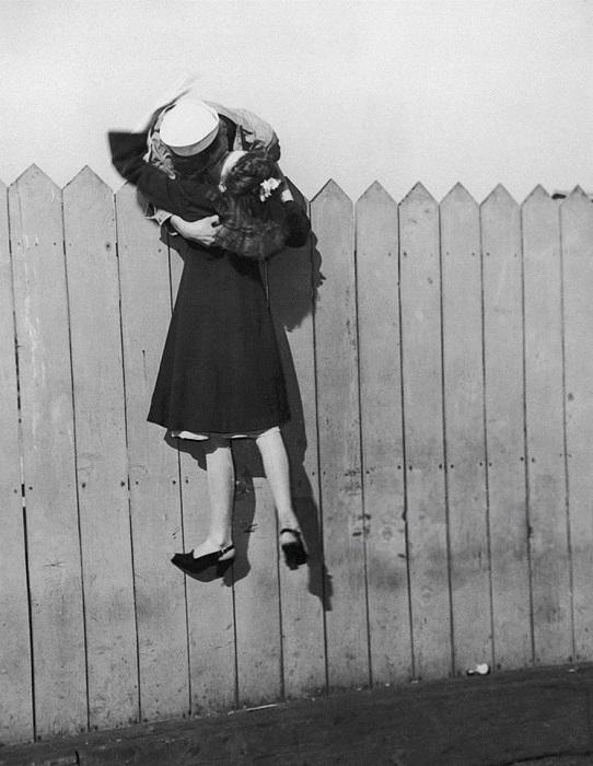 Моряк наклоняется через забор и поднимает девушку, чтобы поцеловать, 1945 год.