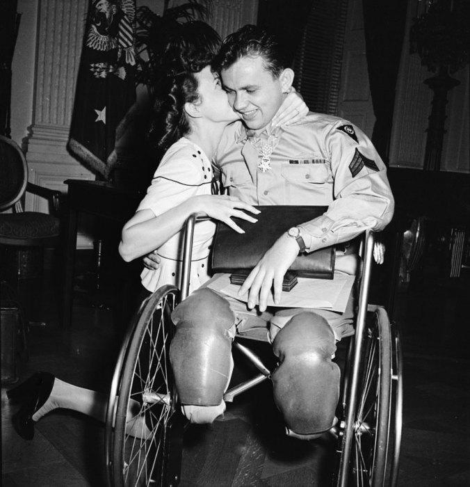 Девушка целует жениха вернувшегося с войны в инвалидной коляске, 1945 год.
