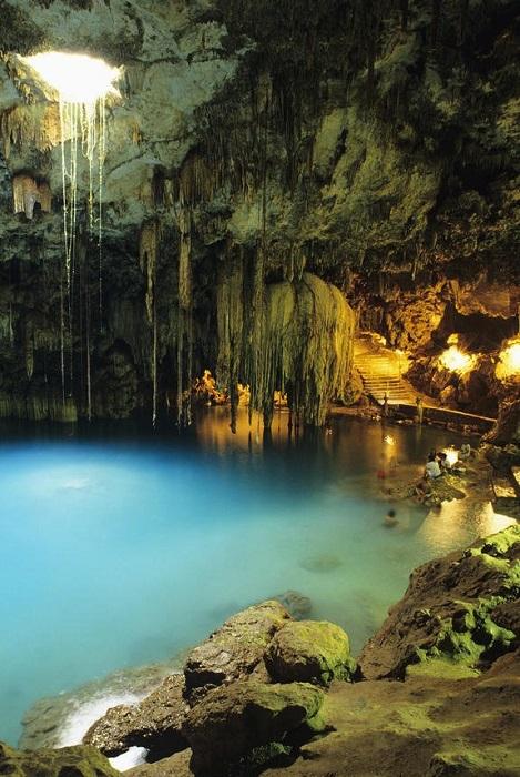 Естественный водоем, питаемый подземными водами с причудливыми корнями огромного дерева, спускающимися вниз через известняковый провал.