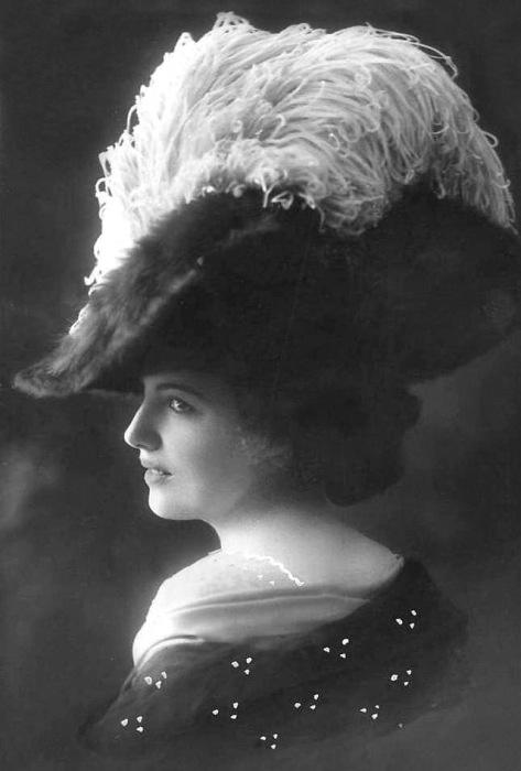 Шляпа женщины с огромными полями из бархата, украшенная кружевом и страусиными перьями.