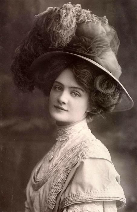 Девушка в шляпе с небольшими полями, украшенная тонкой прозрачной тканью и перьями.