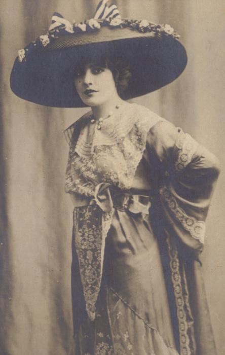 Шляпа с большими полями, украшенная цветами и бантом, подходит для пеших прогулок в летнюю пору.