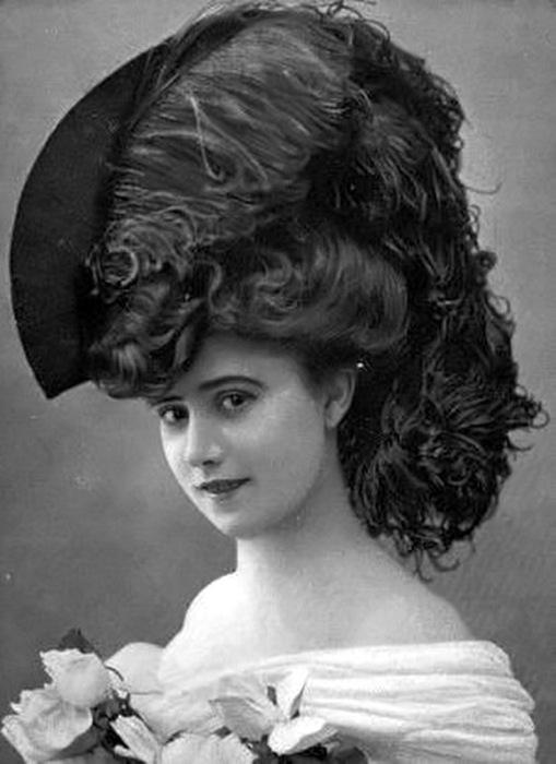 Романтичный образ девушки в необычной шляпке, поля которой с одной стороны приподняты и украшены черным пером.