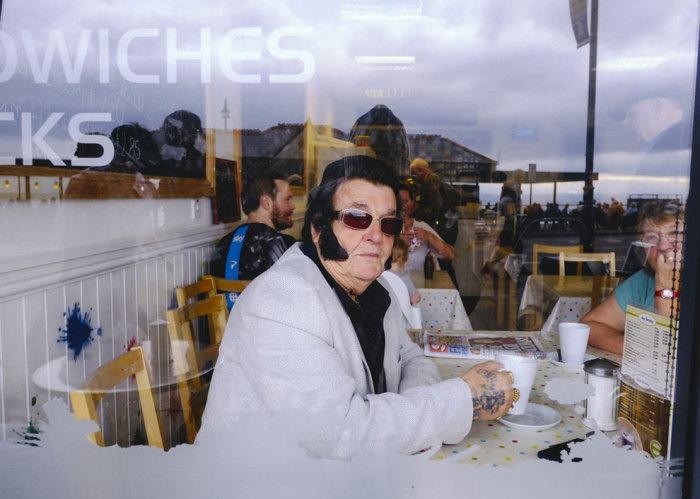 Мужчина в белом пиджаке и очках пьет капучино в кафе.