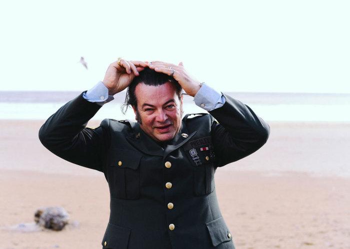 Мужчина на берегу океана, приглаживающий свои волосы, очень похож на короля рок-н-рола.
